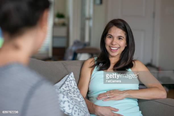 Ethnic pregnant mother laughing with a friend at home