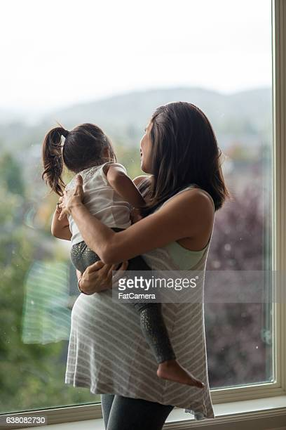 Ethnic pregnant mother playing with her daughter in their home