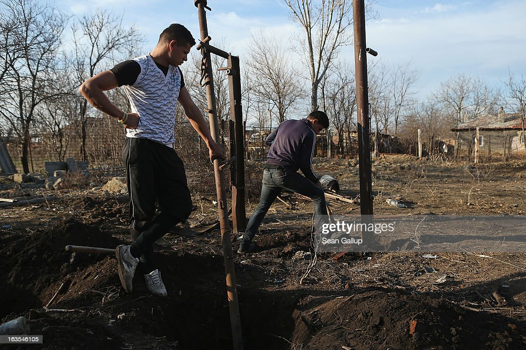 Ethnic Roma Costin Costea (L), 19, and his brother Florin, 17, dig out iron columns that were part of a shed to make way for a vegetable garden on the property of their father on March 11, 2013 in Dilga, Romania. Costin recently finished high school and is looking for a job, and both brothers are helping their father Marian to build a house. Marian worked for two years in Italy as a construction worker until he lost his job as the Italian economy declined. Dilga is a settlement of 2,500 people with dirt roads and no running water, and unemployment is at 70%. Most of the working-age men and women have at some point worked abroad, mostly in Italy or Great Britain, as many say they are unable to find adequate work in Romania. Romania's Roma belong to a myriad of different tribes defined by their craft, and Dilga's belong to a group called the Rudari, who until the 1930s specialised in woodcrafts. During the communist years most worked in nearby state-run factories and agricultural cooperatives, though the majority of these went bankrupt after 1989 and the local Roma lost their jobs. Since then they have struggled to make ends meet and find a better future for their children, though projects initiated by the European Union and NGOs are helping some to launch small-scale enterprises and improve their children's education.