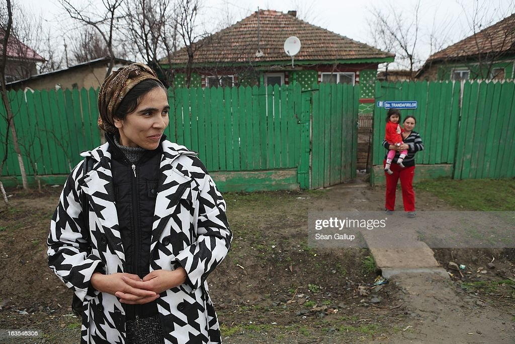 Ethnic Roma, including Viorica Gheorghe (R) and her daughter Gabriela, 3, stand outside the Gheorghe home on March 11, 2013 in Dilga, Romania. Viorica's husband works in Bucharest, a two-hour train commute away, and the couple, their two children and his mother surive on his salary of EUR 200 a month. Dilga is a settlement of 2,500 people with dirt roads and no running water, and unemployment is at 70%. Most of the working-age men and women have at some point worked abroad, mostly in Italy or Great Britain, as many say they are unable to find adequate work in Romania. Romania's Roma belong to a myriad of different tribes defined by their craft, and Dilga's belong to a group called the Rudari, who until the 1930s specialised in woodcrafts. During the communist years most worked in nearby state-run factories and agricultural cooperatives, though the majority of these went bankrupt after 1989 and the local Roma lost their jobs. Since then they have struggled to make ends meet and find a better future for their children, though projects initiated by the European Union and NGOs are helping some to launch small-scale enterprises and improve their children's education.