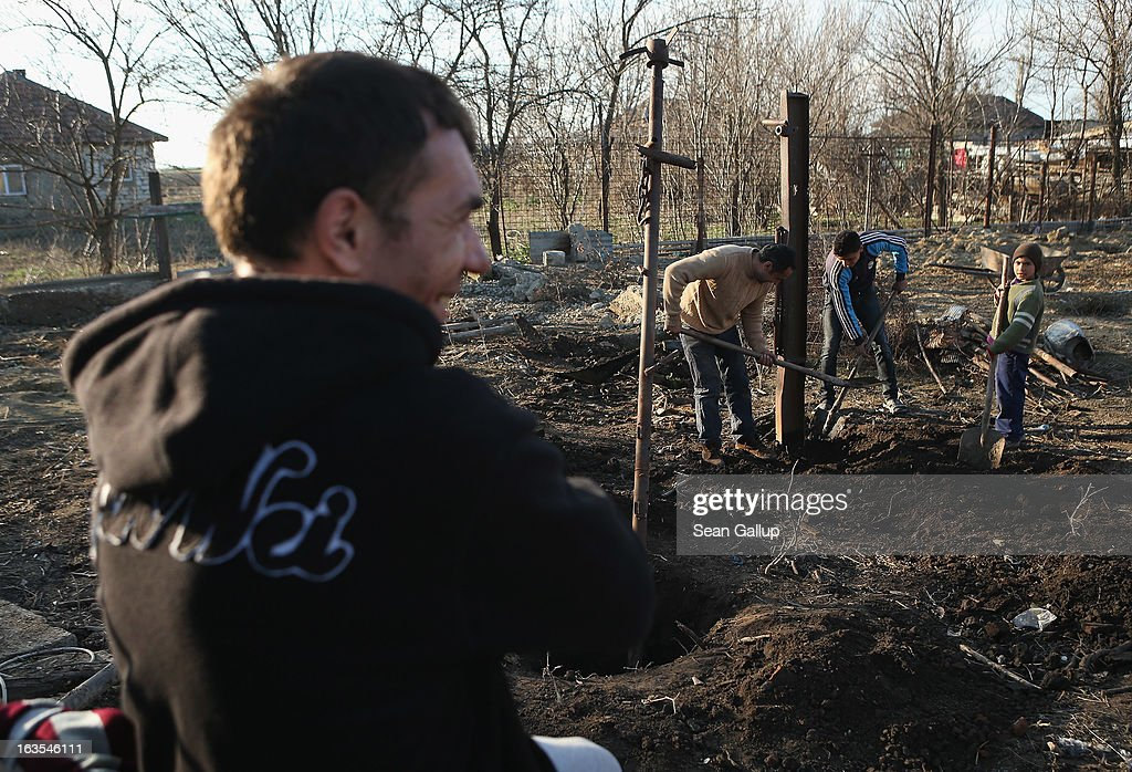 Ethnic Roma Marian Costea watches as his sons and a relative dig out iron columns that were part of a shed to make way for a vegetable garden on his property on March 11, 2013 in Dilga, Romania. Marian worked for years in Italy as a construction worker, though had to give that up and return to Dilga, where he is building a house for him and his family, following an injury to his spine. Dilga is a settlement of 2,500 people with dirt roads and no running water, and unemployment is at 70%. Most of the working-age men and women have at some point worked abroad, mostly in Italy or Great Britain, as many say they are unable to find adequate work in Romania. Romania's Roma belong to a myriad of different tribes defined by their craft, and Dilga's belong to a group called the Rudari, who until the 1930s specialised in woodcrafts. During the communist years most worked in nearby state-run factories and agricultural cooperatives, though the majority of these went bankrupt after 1989 and the local Roma lost their jobs. Since then they have struggled to make ends meet and find a better future for their children, though projects initiated by the European Union and NGOs are helping some to launch small-scale enterprises and improve their children's education.