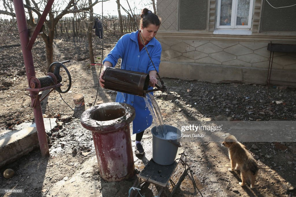 Ethnic Roma Mihaela Boboaca gets water from her well outside her home on March 11, 2013 in Dilga, Romania. Mihaela has worked as a migrant worker in Spain picking strawberries for three consecutive years, though she says she is taking a break as she is pregnant with her third child. Dilga is a settlement of 2,500 people with dirt roads and no running water, and unemployment is at 70%. Most of the working-age men and women have at some point worked abroad, mostly in Italy or Great Britain, as many say they are unable to find adequate work in Romania. Romania's Roma belong to a myriad of different tribes defined by their craft, and Dilga's belong to a group called the Rudari, who until the 1930s specialised in woodcrafts. During the communist years most worked in nearby state-run factories and agricultural cooperatives, though the majority of these went bankrupt after 1989 and the local Roma lost their jobs. Since then they have struggled to make ends meet and find a better future for their children, though projects initiated by the European Union and NGOs are helping some to launch small-scale enterprises and improve their children's education.