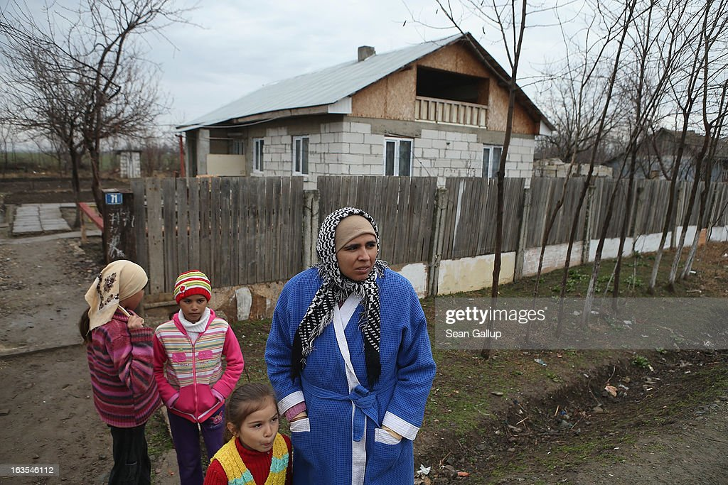 Ethnic Roma Mirela Tudor and three of her five children stand outside the new house her partner Mitica Tenase built on March 11, 2013 in Dilga, Romania. Mitica worked in Manchester in Great Britain at a metals recycling company and now works in construction in Romania. Dilga is a settlement of 2,500 people with dirt roads and no running water, and unemployment is at 70%. Most of the working-age men and women have at some point worked abroad, mostly in Italy or Great Britain, as many say they are unable to find adequate work in Romania. Romania's Roma belong to a myriad of different tribes defined by their craft, and Dilga's belong to a group called the Rudari, who until the 1930s specialised in woodcrafts. During the communist years most worked in nearby state-run factories and agricultural cooperatives, though the majority of these went bankrupt after 1989 and the local Roma lost their jobs. Since then they have struggled to make ends meet and find a better future for their children, though projects initiated by the European Union and NGOs are helping some to launch small-scale enterprises and improve their children's education.