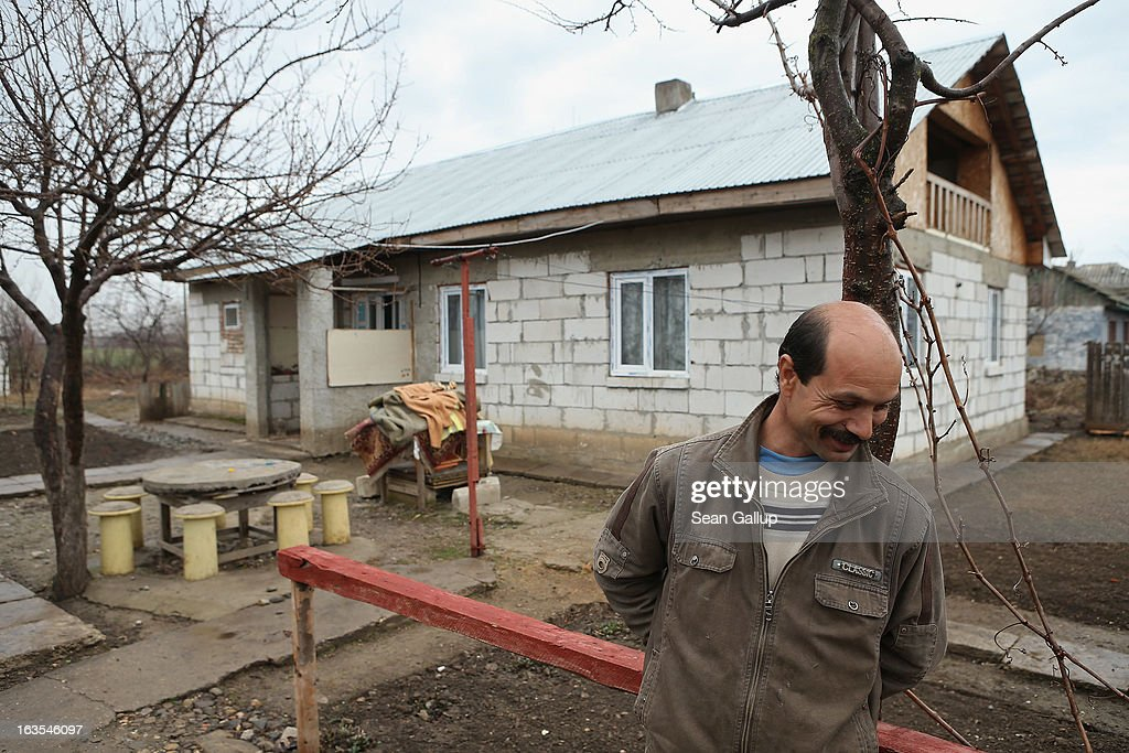 Ethnic Roma Mitica Tanase stands outside the new house he built for himself, his partner and their five children on March 11, 2013 in Dilga, Romania. Mitica worked in Manchester in Great Britain at a metals recycling company and now works in construction in Romania. Dilga is a settlement of 2,500 people with dirt roads and no running water, and unemployment is at 70%. Most of the working-age men and women have at some point worked abroad, mostly in Italy or Great Britain, as many say they are unable to find adequate work in Romania. Romania's Roma belong to a myriad of different tribes defined by their craft, and Dilga's belong to a group called the Rudari, who until the 1930s specialised in woodcrafts. During the communist years most worked in nearby state-run factories and agricultural cooperatives, though the majority of these went bankrupt after 1989 and the local Roma lost their jobs. Since then they have struggled to make ends meet and find a better future for their children, though projects initiated by the European Union and NGOs are helping some to launch small-scale enterprises and improve their children's education.