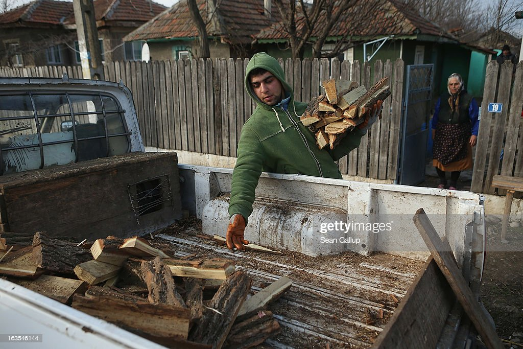Ethnic Roma Serghei Percu, 22, delivers firewood to local elderly Roma resident Aurica Boboaca on March 11, 2013 in Dilga, Romania. Serghei and his brother Victor buy the wood from a local company, then chop it up into firewood and deliver it at a small proft. They operate their enterprise as a business initiated by the Romania office of the Soros Center, the NGO of billionaire investor George Soros, that is supporting small enterprise projects among the rural poor across Romania. Dilga is a settlement of 2,500 people with dirt roads and no running water, and unemployment is at 70%. Most of the working-age men and women have at some point worked abroad, mostly in Italy or Great Britain, as many say they are unable to find adequate work in Romania. Romania's Roma belong to a myriad of different tribes defined by their craft, and Dilga's belong to a group called the Rudari, who until the 1930s specialised in woodcrafts. During the communist years most worked in nearby state-run factories and agricultural cooperatives, though the majority of these went bankrupt after 1989 and the local Roma lost their jobs. Since then they have struggled to make ends meet and find a better future for their children, though projects initiated by the European Union and NGOs are helping some to launch small-scale enterprises and improve their children's education.