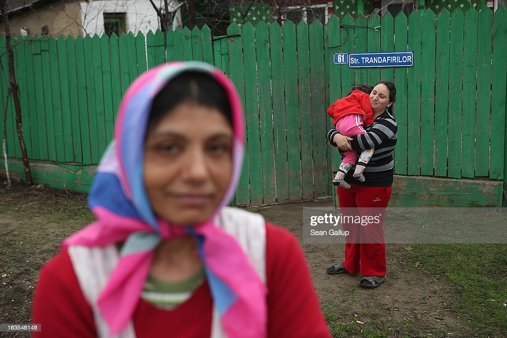 Ethnic Roma Tudora Tanase (L), Viorica Gheorghe and Viorica's daughter Gabriela, 3, stand outside the Gheorghe home on March 11, 2013 in Dilga, Romania. Viorica's husband works in Bucharest, a two-hour train commute away, and the couple, their two children and his mother surive on his salary of EUR 200 a month, while Tudora works as a cleaning woman at a Bucharest university. Dilga is a settlement of 2,500 people with dirt roads and no running water, and unemployment is at 70%. Most of the working-age men and women have at some point worked abroad, mostly in Italy or Great Britain, as many say they are unable to find adequate work in Romania. Romania's Roma belong to a myriad of different tribes defined by their craft, and Dilga's belong to a group called the Rudari, who until the 1930s specialised in woodcrafts. During the communist years most worked in nearby state-run factories and agricultural cooperatives, though the majority of these went bankrupt after 1989 and the local Roma lost their jobs. Since then they have struggled to make ends meet and find a better future for their children, though projects initiated by the European Union and NGOs are helping some to launch small-scale enterprises and improve their children's education.