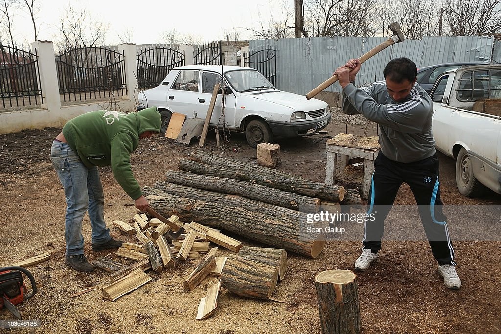 Ethnic Roma Victor Percu (R), 24, and his brother Serghei, 22, chop wood that they bought locally and will deliver as firewood to local families on March 11, 2013 in Dilga, Romania. The two brothers operate their firewood delivery enterprise as a small business initiated by the Romania office of the Soros Center, the NGO of billionaire investor George Soros, that is supporting small enterprise projects among the rural poor across Romania. Victor previously worked for five months in Birmingham in Great Britain. Dilga is a settlement of 2,500 people with dirt roads and no running water, and unemployment is at 70%. Most of the working-age men and women have at some point worked abroad, mostly in Italy or Great Britain, as many say they are unable to find adequate work in Romania. Romania's Roma belong to a myriad of different tribes defined by their craft, and Dilga's belong to a group called the Rudari, who until the 1930s specialised in woodcrafts. During the communist years most worked in nearby state-run factories and agricultural cooperatives, though the majority of these went bankrupt after 1989 and the local Roma lost their jobs. Since then they have struggled to make ends meet and find a better future for their children, though projects initiated by the European Union and NGOs are helping some to launch small-scale enterprises and improve their children's education.