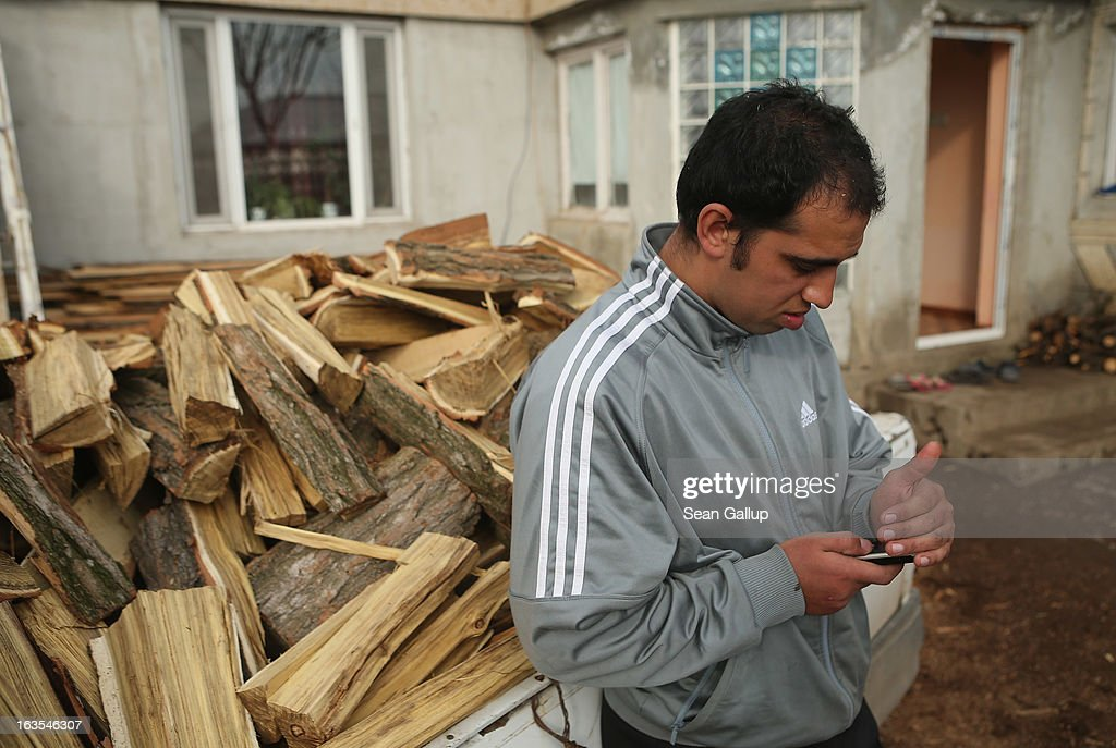 Ethnic Roma Victor Percu, 24, checks messages on his mobile phone before delivering firewood to a local family on March 11, 2013 in Dilga, Romania. Victor and his brother Serghei buy the wood from a local company, then chop it up into firewood and deliver it at a small proft. They operate their enterprise as a business initiated by the Romania office of the Soros Center, the NGO of billionaire investor George Soros, that is supporting small enterprise projects among the rural poor across Romania. Victor previously worked for five months in Birmingham in Great Britain. Dilga is a settlement of 2,500 people with dirt roads and no running water, and unemployment is at 70%. Most of the working-age men and women have at some point worked abroad, mostly in Italy or Great Britain, as many say they are unable to find adequate work in Romania. Romania's Roma belong to a myriad of different tribes defined by their craft, and Dilga's belong to a group called the Rudari, who until the 1930s specialised in woodcrafts. During the communist years most worked in nearby state-run factories and agricultural cooperatives, though the majority of these went bankrupt after 1989 and the local Roma lost their jobs. Since then they have struggled to make ends meet and find a better future for their children, though projects initiated by the European Union and NGOs are helping some to launch small-scale enterprises and improve their children's education.