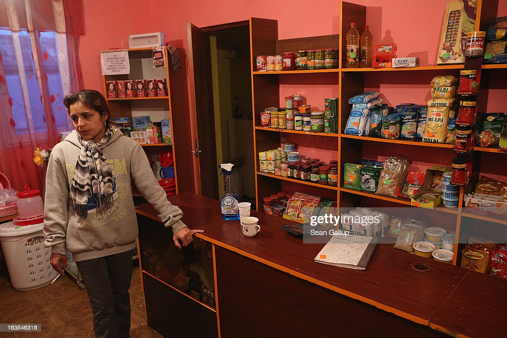 Ethnic Roma Xenia Costea stands in the small grocery shop she runs on March 11, 2013 in Dilga, Romania. Xenia says hers is one of six small shops in Dilga and that many of her customers buy on credit. Dilga is a settlement of 2,500 people with dirt roads and no running water, and unemployment is at 70%. Most of the working-age men and women have at some point worked abroad, mostly in Italy or Great Britain, as many say they are unable to find adequate work in Romania. Romania's Roma belong to a myriad of different tribes defined by their craft, and Dilga's belong to a group called the Rudari, who until the 1930s specialised in woodcrafts. During the communist years most worked in nearby state-run factories and agricultural cooperatives, though the majority of these went bankrupt after 1989 and the local Roma lost their jobs. Since then they have struggled to make ends meet and find a better future for their children, though projects initiated by the European Union and NGOs are helping some to launch small-scale enterprises and improve their children's education.
