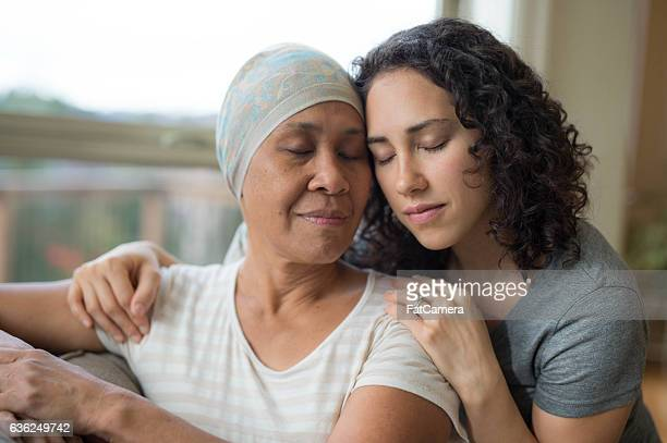 Ethnic senior adult female with cancer being embraced