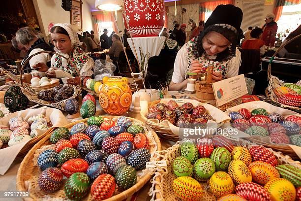 Ethnic Sorbian Heidemarie Hoeft wearing a traditional Upper Lusatian folk dress and black headdress paints an Easter egg in traditional Sorbian...