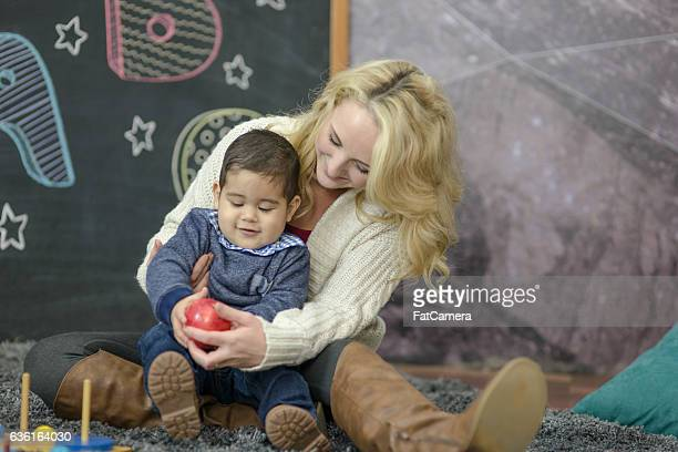 Ethnic toddler playing with his teacher in a daycare