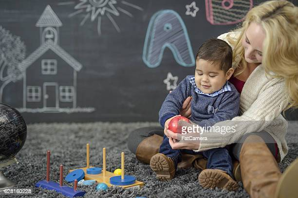 Ethnic toddler playing with his teacher