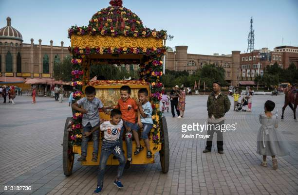 Ethnic Uyghur boys ride on the back of a horse cart on June 28 2017 in the old town of Kashgar in the far western Xinjiang province China Kashgar has...