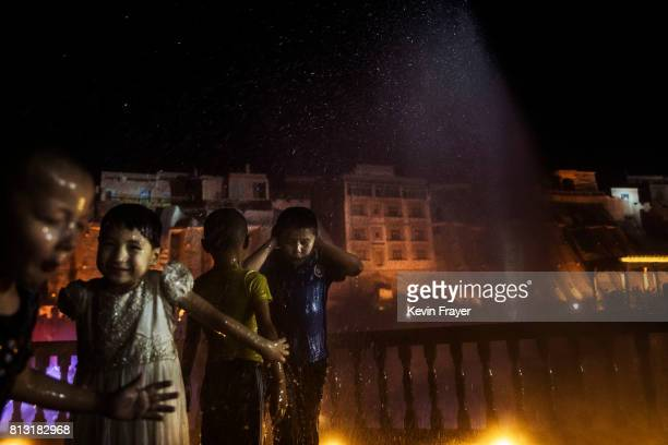 Ethnic Uyghur children get wet as they take part in a new laser and water show as part of local government tourism development on June 30 2017 in the...