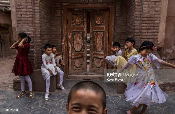 Ethnic Uyghur children sit outside a locked local mosque that was closed by authorities on June 27 2017 in the old town of Kashgar in the far western...