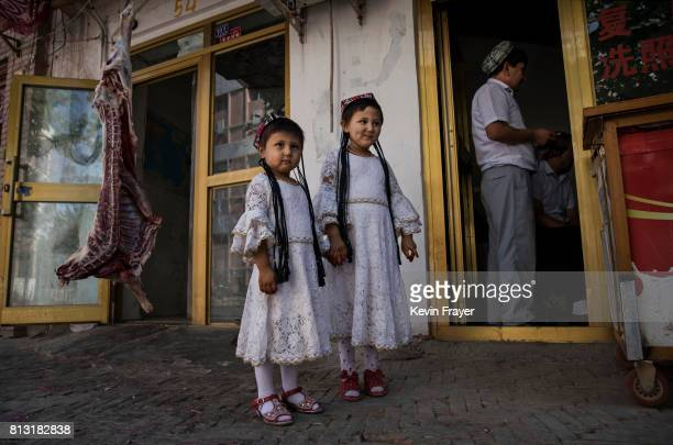 Ethnic Uyghur girls wear traditional clothing as they stand outside a butcher shop on June 29 2017 in the old town of Kashgar in the far western...