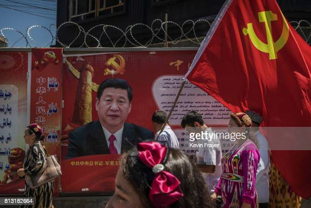 Ethnic Uyghur members of the Communist Party of China carry a flag past a billboard of Chinese President Xi Jinping as they take part in an organized...