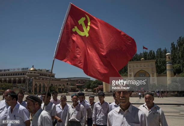 Ethnic Uyghur members of the Communist Party of China carry a flag as they take part in an organized tour outside Id Kah Mosque on June 30 2017 in...