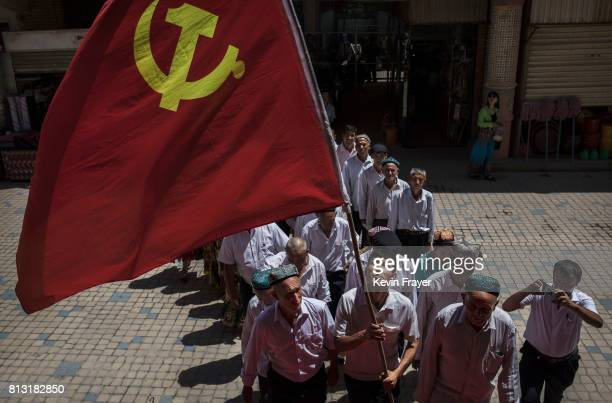 Ethnic Uyghur members of the Communist Party of China carry a flag as they take part in an organized tour on June 30 2017 in the old town of Kashgar...