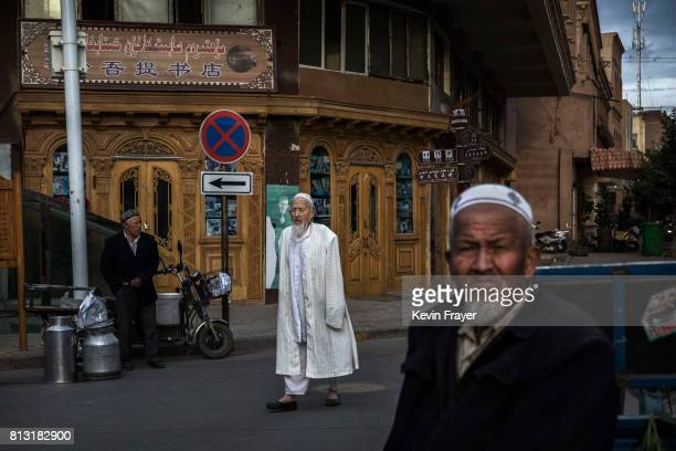 Ethnic Uyghur men are seen in the street at a local market on July 1 2017 in the old town of Kashgar in the far western Xinjiang province China...