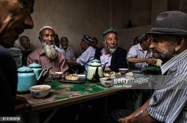 Ethnic Uyghur men talk as they meet at a teahouse on July 1 2017 in the old town of Kashgar in the far western Xinjiang province China Kashgar has...