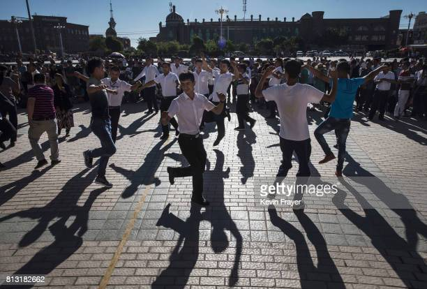 Ethnic Uyghur men who were organized by local party officials dance after prayers marking Eid Al Fitr outside Id Kah Mosque on June 26 2017 in the...