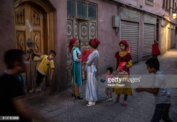 Ethnic Uyghur women talk in the street on June 29 2017 in the old town of Kashgar in the far western Xinjiang province China Kashgar has long been...