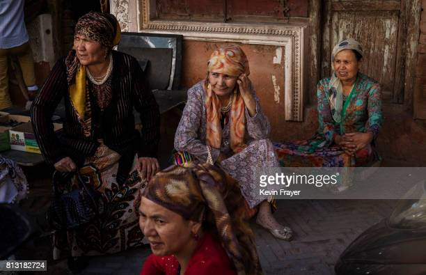 Ethnic Uyghur women wait outside a local government office on June 29 2017 in the old town of Kashgar in the far western Xinjiang province China...