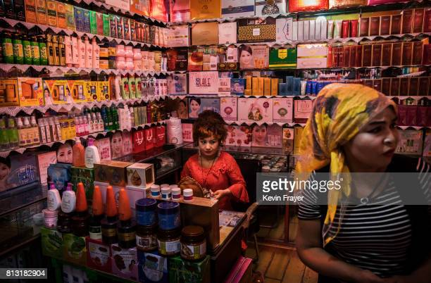 Ethnic Uyghur women work at their beauty supplies shop on July 1 2017 in the old town of Kashgar in the far western Xinjiang province China Kashgar...
