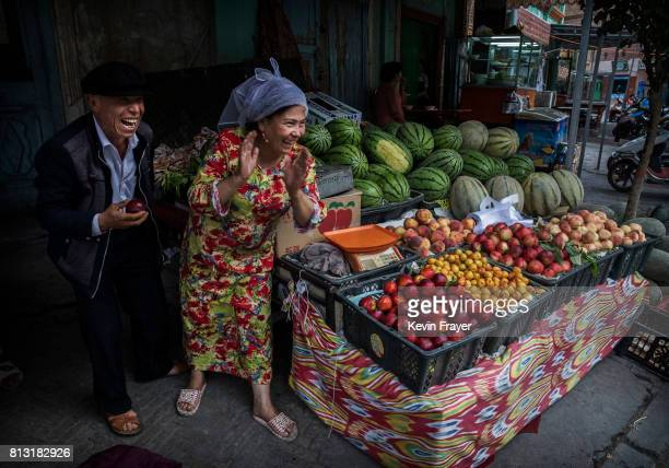 Ethnic Uyghurs joke with a customer at their fruit stall on June 28 2017 in the old town of Kashgar in the far western Xinjiang province China...