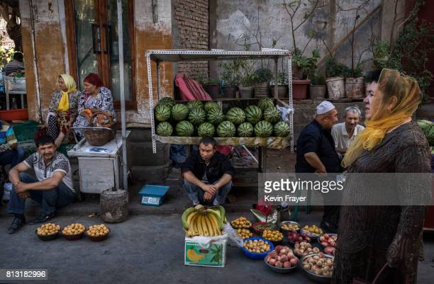 Ethnic Uyghurs sell fruits at a market on June 29 2017 in the old town of Kashgar in the far western Xinjiang province China Kashgar has long been...