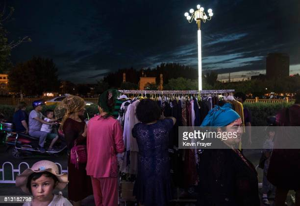 Ethnic Uyghurs shop at a market on the holiday of Eid Al FItr on June 26 2017 in the old town of Kashgar in the far western Xinjiang province China...