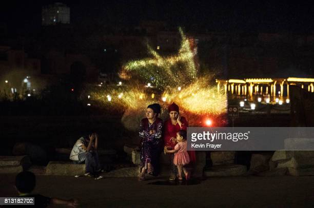 Ethnic Uyghurs sit near a projection in a new laser and water show as part of local government tourism development on June 30 2017 in the old town of...