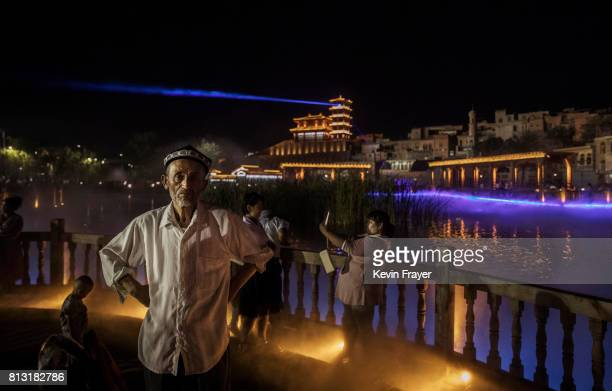Ethnic Uyghurs take in a new laser and water show as part of local government tourism development on June 30 2017 in the old town of Kashgar in the...