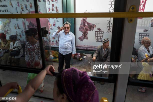Ethnic Uyghurs wait at a bus top to ride local transit on June 30 2017 in the old town of Kashgar in the far western Xinjiang province China Kashgar...