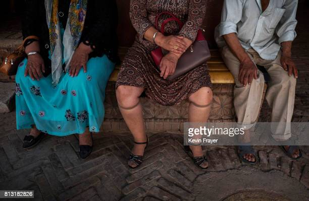 Ethnic Uyghurs wait outside a local government office on June 29 2017 in the old town of Kashgar in the far western Xinjiang province China Kashgar...