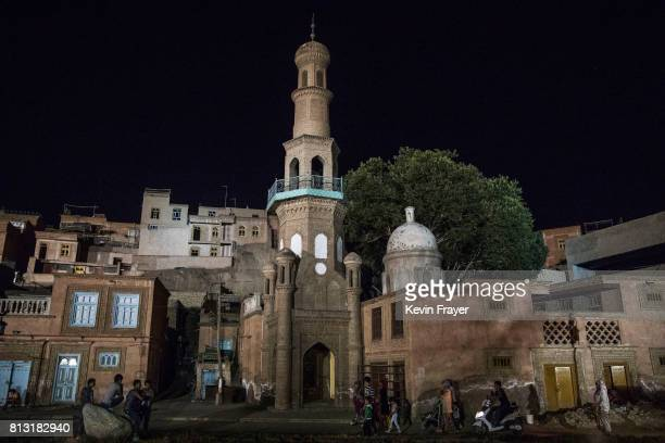 Ethnic Uyghurs walk by a closed mosque on July 1 2017 in the old town of Kashgar in the far western Xinjiang province China Kashgar has long been...