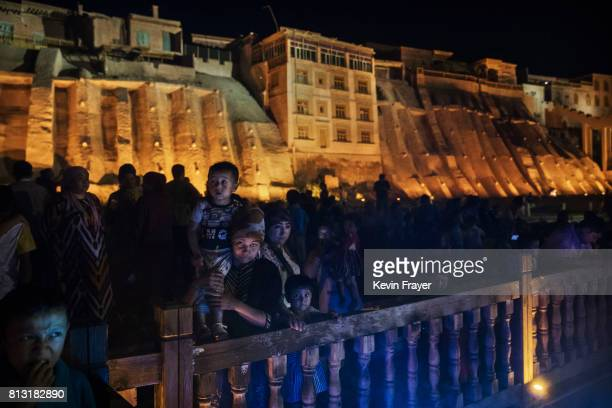 Ethnic Uyghurs watch a new laser and water show as part of local government tourism development on June 30 2017 in the old town of Kashgar in the far...
