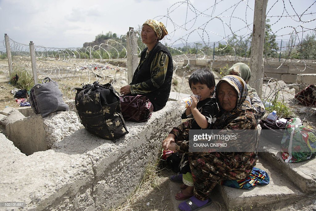 Ethnic Uzbek women refugees sit near a barbed wire fence in camp 10 km outside of Osh in Nariman on June 15 2010 on the border with Uzbekistan...