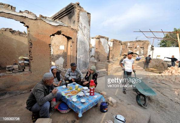 Ethnic Uzbeks have a dinner near their destroyed house in Osh on October 7 2010 Kyrgyzstan is on high alert to avoid any upsurge of violence ahead of...