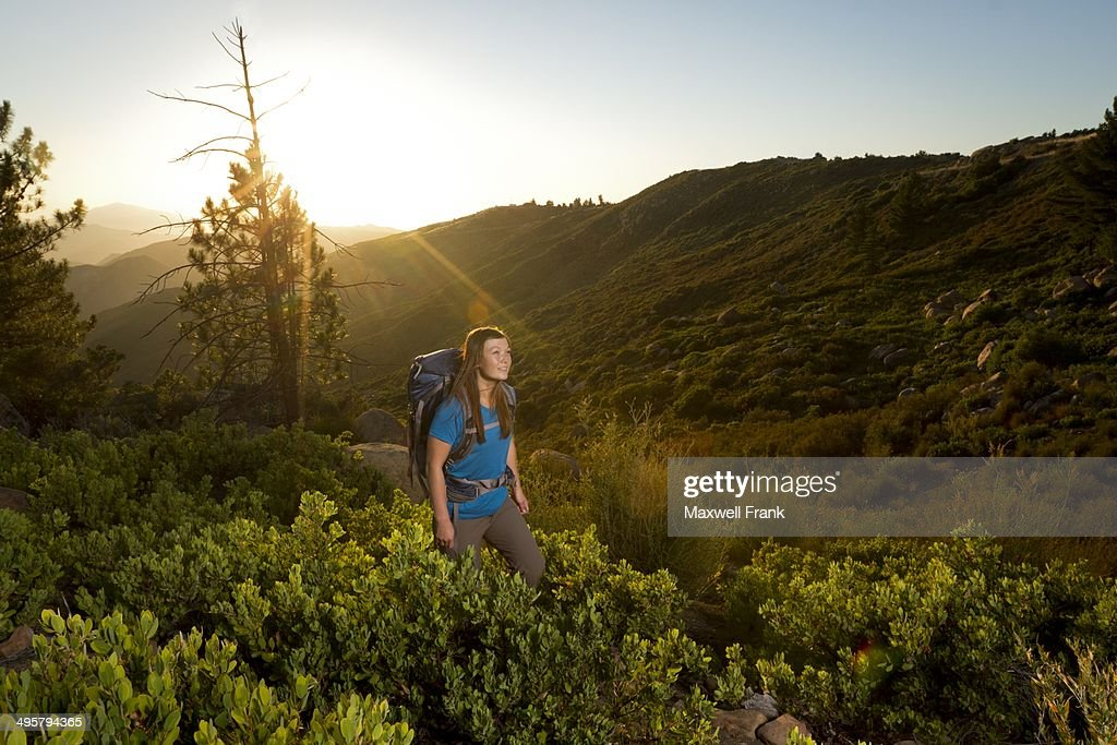 Ethnic woman backpacking in the mountains through chaparral.