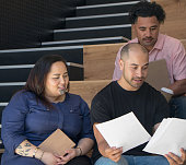 Ethnically diverse group of employees in business work place having a serious team meeting reviewing a document. Photographed in Auckalnd, New Zealand, NZ.