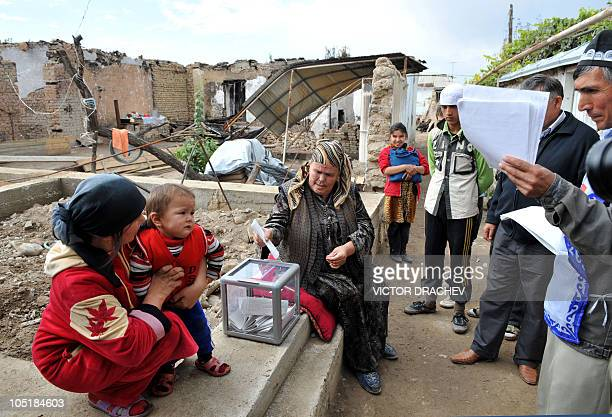 Ethnik uzbek vote near their destroyed houses in Osh on October 10 2010 President Roza Otunbayeva vowed Kyrgyzstan's elections Sunday for a...