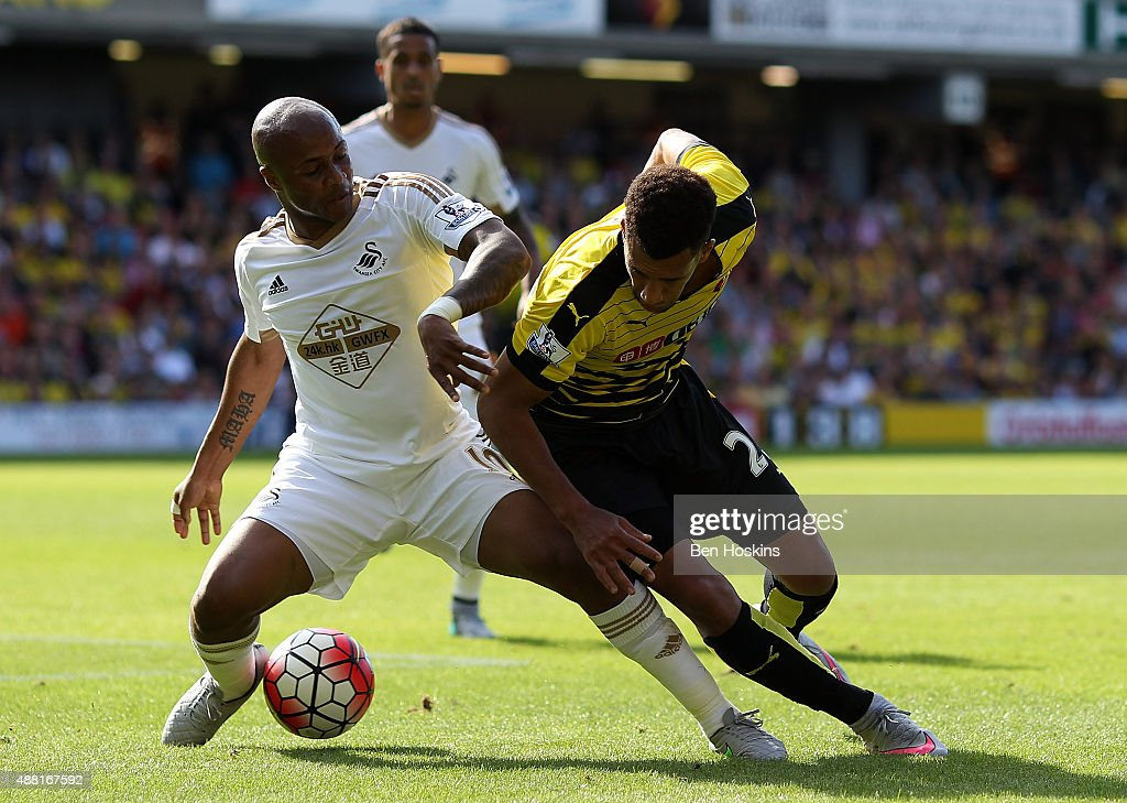 Etienne Capoue of Watford is tackled by Andre Ayew of Swansea during the Barclays Premier League match between Watford and Swansea City at Vicarage...