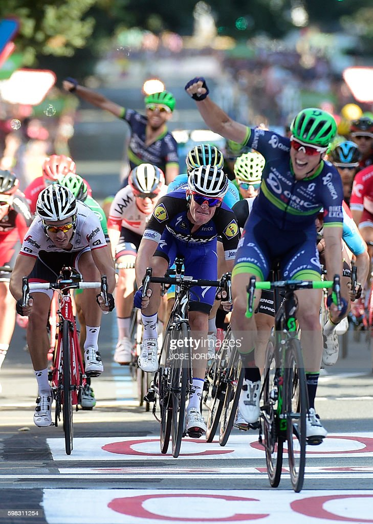 Etixx-Quick Step's French cyclist Maxime Bouet (C) looks at Orica Bikeexchange's Belgian cyclist Jens Keukeleire (R) celebrating as he crosses the finish line to win the 12th stage of the 71st edition of 'La Vuelta' Tour of Spain, a 193.2km route between Los Corrales de Buelna and Bilbao, on September 1, 2016. / AFP / JOSE