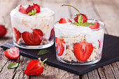 Eton Mess - Strawberries with whipped cream and meringue in a glass beaker. Classic British summer dessert.selective focus