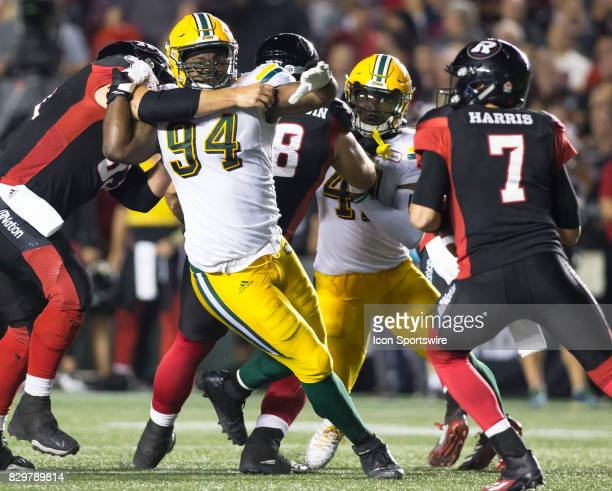 Euclid Cummings of the Edmonton Eskimos breaks through the Ottawa Redblacks offensive line to rush quarterback Trevor Harris in Canadian Football...