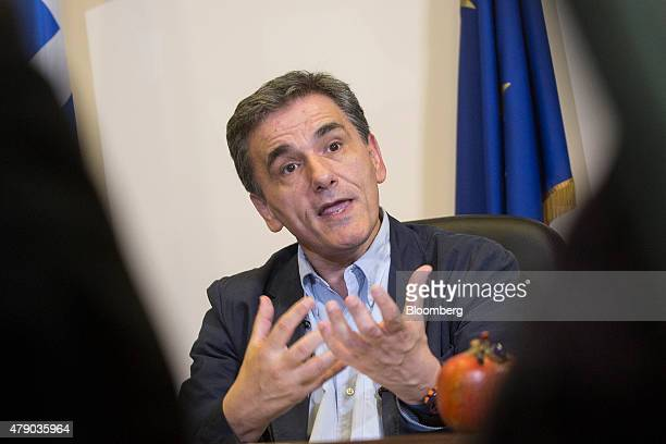 Euclid Tsakalotos Greece's deputy foreign minister gestures whilst speaking during a Bloomberg Television interview at his office in Athens Greece on...