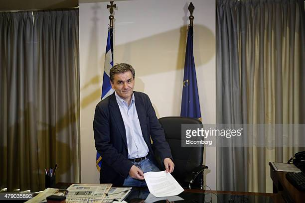 Euclid Tsakalotos Greece's deputy foreign minister stands by his desk during a Bloomberg Television interview at his office in Athens Greece on...